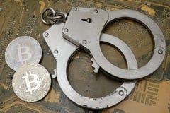 O conceito de uma violação da lei, cibercrime, fraude financeira Duas moedas do bitcoin e as algemas encontram-se no fundo do fotos de stock