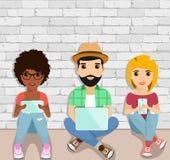 O conceito de usuários ativos dos dispositivos Jovens que sentam-se no assoalho usando dispositivos Povos felizes Foto de Stock Royalty Free