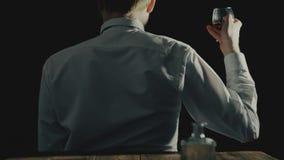 O conceito do alcoólico anônimo e do alcoolismo ou a desordem do uso do álcool, homem sentam-se com o o seu de volta à câmera filme