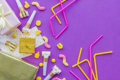 O conceito do aniversário com presentes, cartões e partido assobia no copyspace violeta da opinião superior do fundo Foto de Stock Royalty Free