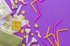 O conceito do aniversário com presentes, cartões e partido assobia no copyspace violeta da opinião superior do fundo Fotografia de Stock Royalty Free