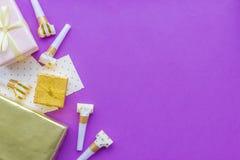 O conceito do aniversário com presentes, cartões e partido assobia no copyspace violeta da opinião superior do fundo Fotos de Stock