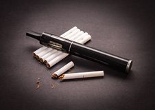 O conceito do atomizador anti-fumaça está no isolado do cigarro no fundo escuro imagens de stock