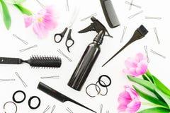 O conceito do cabeleireiro com pulverizador, tesouras, pentes, prendedor de cabelo e tulipas floresce no fundo branco Conceito da Fotografia de Stock Royalty Free