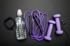 O conceito do cardio- treinamento Pesos, corda do jamp, fones de ouvido, bracelete da aptidão e água Fundo preto fotos de stock royalty free