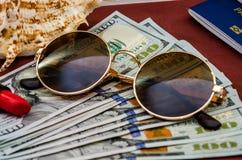 O conceito do curso com passaportes, dólares e vidros fotos de stock