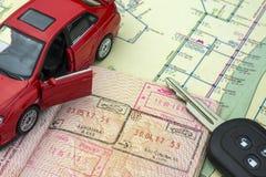 O conceito do curso de carro: o passaporte com os selos da beira Chaves do mapa e do carro da cidade Modelo vermelho do carro fotos de stock royalty free