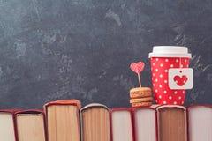 O conceito do dia de Valentim com o copo de café, macarons e vintage de papel registra sobre o quadro-negro Foto de Stock