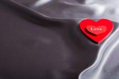 O conceito do dia de Valentim, corações vermelhos ama no fundo cinzento de seda Fotografia de Stock Royalty Free