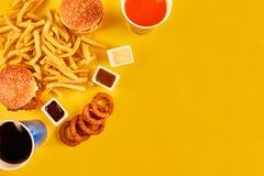 O conceito do fast food com o restaurante fritado gorduroso remove como anéis de cebola, hamburguer, frango frito e batatas frita imagens de stock royalty free