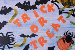 O conceito do feriado de Dia das Bruxas bastões e doces em um fundo azul com uma opinião superior da doçura ou travessura da insc fotografia de stock