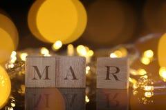 O conceito do mês, vista dianteira mostra o bloco de madeira escrito março com li Imagem de Stock