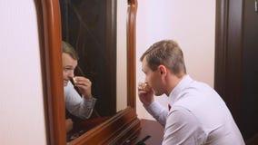 O conceito do metrosexualism um homem considerável na frente de um espelho toma de sua cara faz o contorno do fotografia de stock