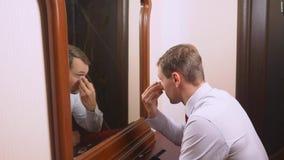 O conceito do metrosexualism um homem considerável na frente de um espelho toma de sua cara faz o contorno do imagem de stock