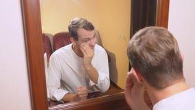 O conceito do metrosexualism um homem considerável na frente de um espelho toma de sua cara faz o contorno do fotos de stock