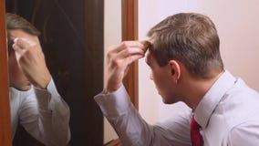 O conceito do metrosexualism um homem considerável na frente de um espelho toma de sua cara faz o contorno do imagem de stock royalty free