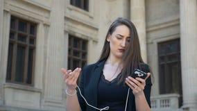 O conceito do movimento lento da terra arrendada da mulher de negócio descarregou o smartphone e o carregador video estoque