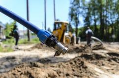 O conceito do trator, o trator escava e enterra uma trincheira para colocar a ?gua em um lote da floresta para a constru??o da ca fotografia de stock