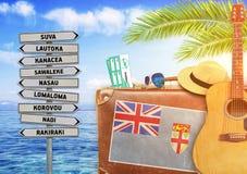 O conceito do verão que viajam com mala de viagem velha e a cidade de Fiji assinam Fotografia de Stock Royalty Free