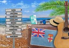 O conceito do verão que viajam com mala de viagem velha e a cidade de Fiji assinam Imagens de Stock Royalty Free