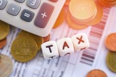 O conceito e a calculadora do imposto empilharam moedas no papel da conta da fatura para o pagamento pago de enchimento do d?bito fotos de stock