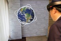 O conceito industrial da tecnologia da educação esperta, homem borrou usando vidros espertos estuda sobre o mundo/globo em 3d usa Fotografia de Stock