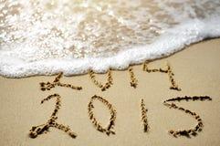 O conceito próximo feliz 2015 do ano substitui 2014 na praia do mar Foto de Stock Royalty Free