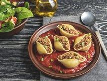 O conchiglioni cozinhado da massa encheu a carne triturada, molho de tomate na placa foto de stock