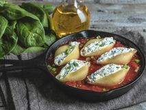 o conchiglioni da massa encheu espinafres e queijo, molho de tomate cozinhado fotografia de stock