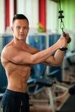 O concorrente da aptidão de Phisique dá certo em pesos de levantamento do gym Imagem de Stock