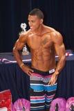 O concorrente masculino da aptidão mostra seu melhor físico na fase Imagens de Stock