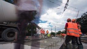 O concreto trabalha para a construção da manutenção de estrada com muitos trabalhadores e hyperlapse do timelapse do misturador filme