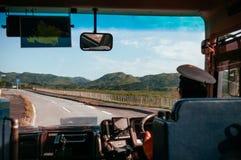 O condutor de ônibus está conduzindo com mãos no volante no asph vazio fotografia de stock