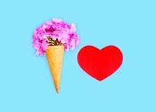 O cone de gelado com flores e o coração vermelho dão forma sobre o fundo colorido azul Foto de Stock Royalty Free