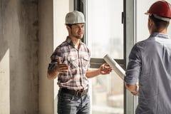 O construtor ambicioso novo no chapéu protetor está pensando sobre os problemas da construção foto de stock