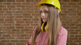 O construtor bonito novo da menina inclina-se sua cabeça, processo de pensamento, fundo do tijolo filme