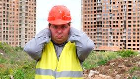 O construtor considerável novo está receoso que o homem cobre suas orelhas com as mãos - canteiro de obras video estoque
