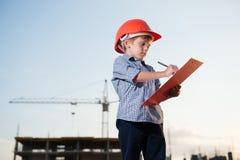 O construtor da criança que veste o capacete alaranjado toma notas no fundo do terreno de construção Fotografia de Stock