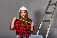 O construtor da mulher guarda a fita métrica fotografia de stock