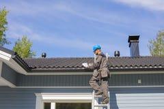 O construtor está em uma escada e usa a fita métrica em Finlandia Imagem de Stock Royalty Free