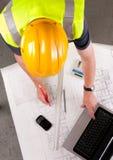 O construtor inspeciona plantas da construção. Fotos de Stock