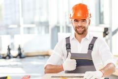 O construtor masculino atrativo está trabalhando com de madeira foto de stock royalty free