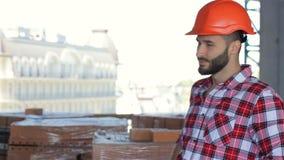 O construtor masculino corrige seu capacete de segurança na construção sob a construção video estoque