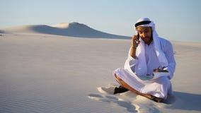 O construtor masculino seguro do xeique dos UAE do Arabian fala em celular com o cliente, sentando-se sobre lixa com o desenho de filme