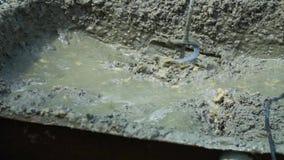 O construtor mistura o emplastro concreto com o misturador elétrico Preparação do concreto no manual vídeos de arquivo