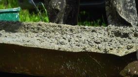 O construtor mistura o emplastro concreto com o misturador elétrico Preparação do concreto no manual video estoque