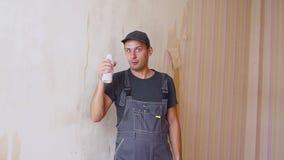 O construtor ou o trabalhador da construção com prazer bebem de uma garrafa branca dentro da construção sob a construção video estoque