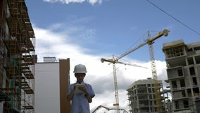 O construtor que o menino está entre guindastes do construtor usando a tabuleta, menino joga um construtor fotos de stock