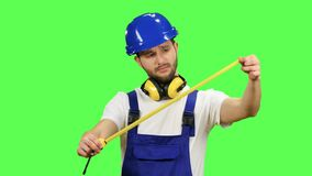 O construtor toma medidas com a ajuda de uma fita métrica Tela verde video estoque