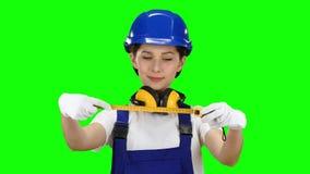 O construtor toma medidas com a ajuda de uma fita métrica Tela verde Fim acima vídeos de arquivo